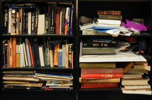 A messy bookshelf with lots of books