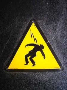 A sign with an image of a man being shocked