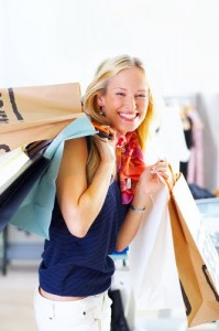 Smiling woman holding many shopping bags